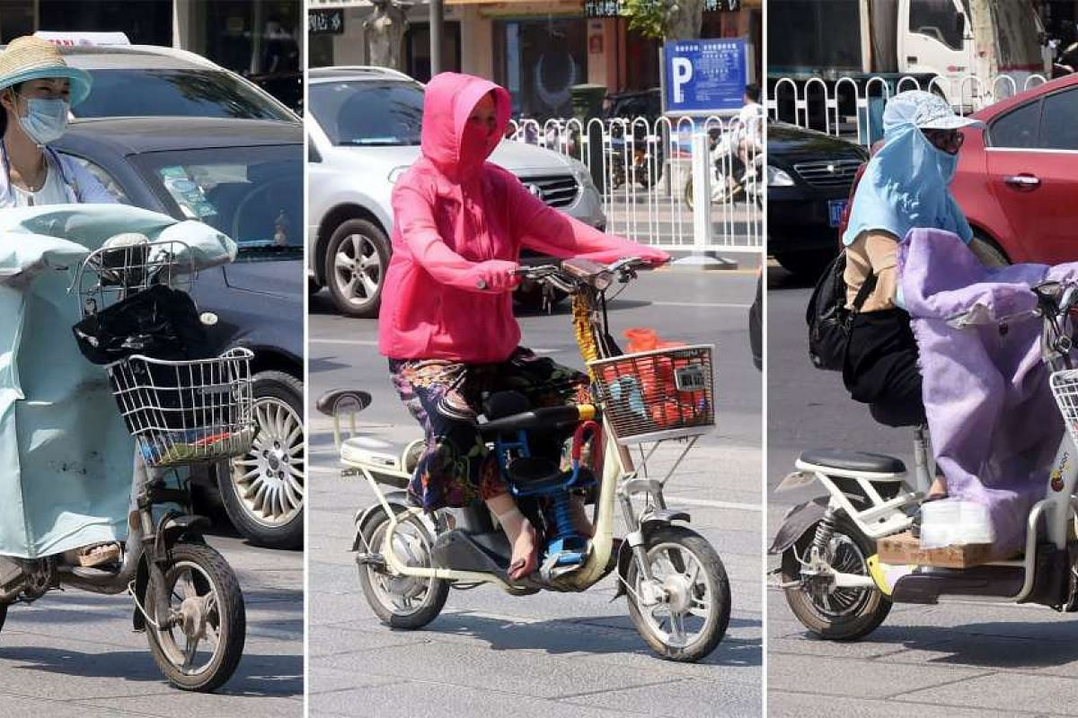 People riding electric bicycles while wearing sun protection clothing in Handan, Hebei province, on July 11, 2017. The summer heatwave is forecast to continue and expand over more of China, with people being warned to protect themselves from the sun.