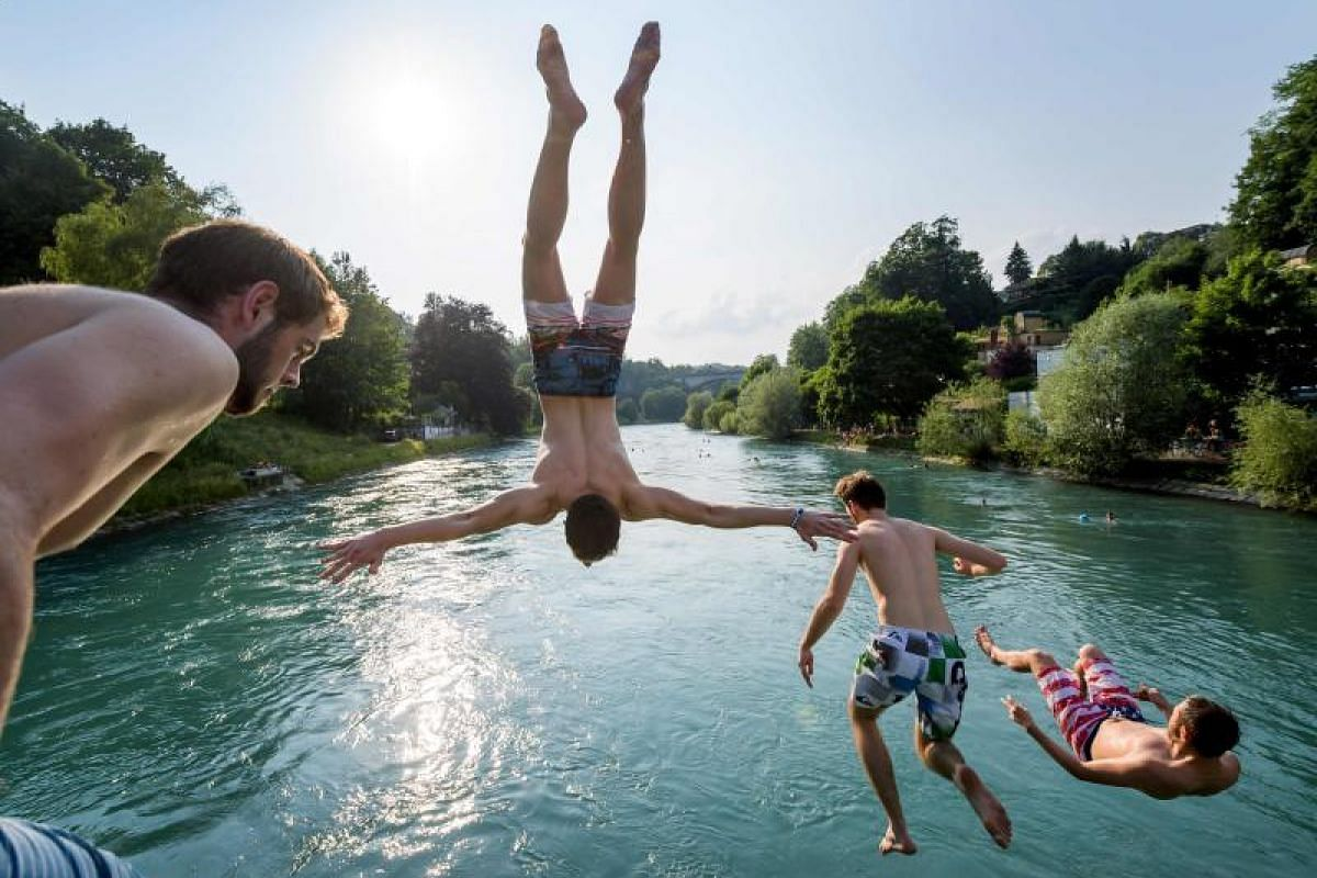 Young men jump into the river Aare on June 21, 2017, in Bern. Europe sizzled in a continent-wide heatwave, with London bracing for Britain's hottest June day since 1976 as Portugal battled to stamp out deadly forest fires. Cooler weather was aiding t