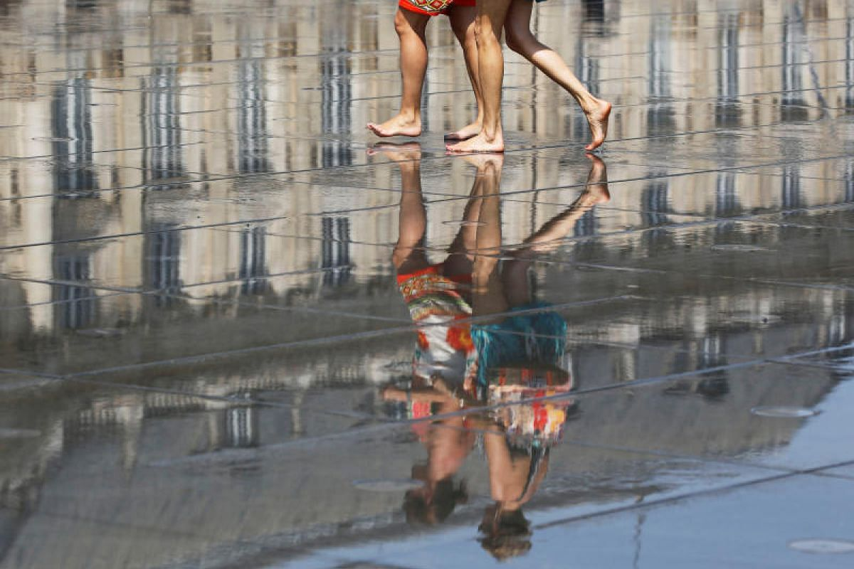 People cool off as they walk on a water mirror on the Place de la Bourse in Bordeaux as hot summer temperatures hit France on June 22, 2017.