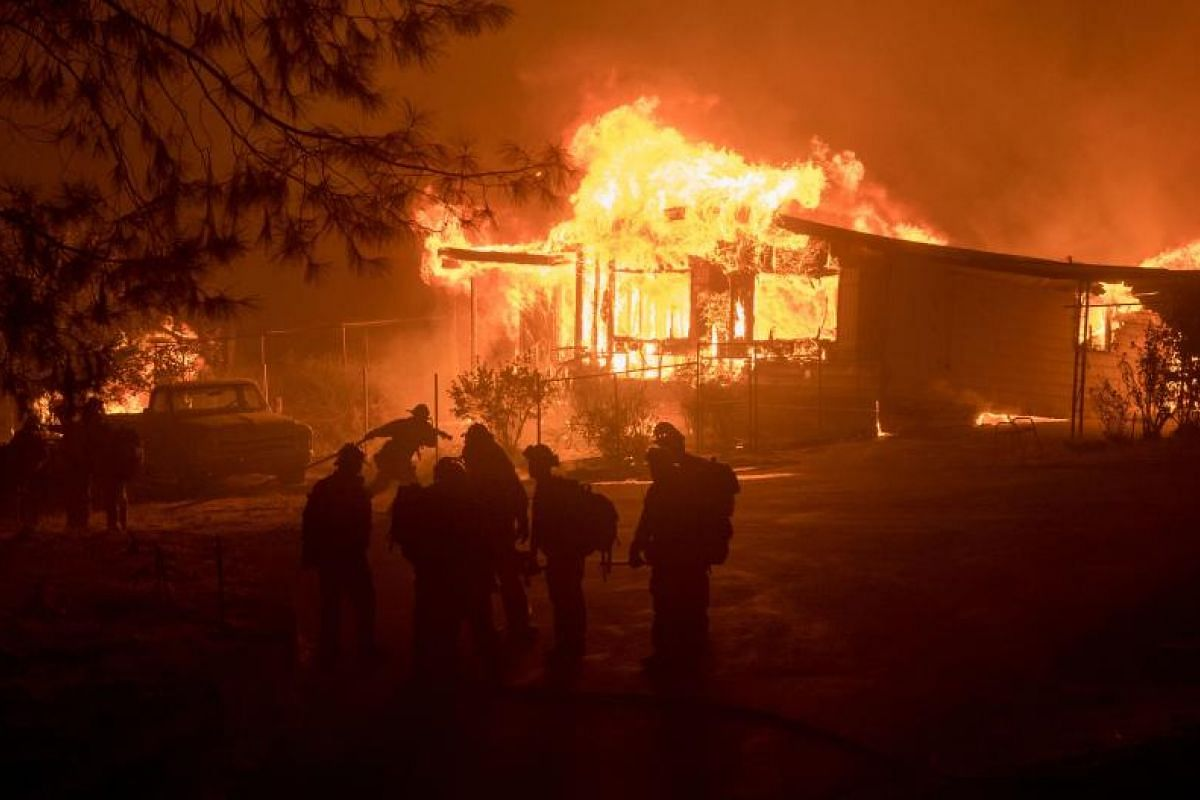 A firefighter carries a hose as a house burns in Oroville, California, on July 8, 2017. The first major wildfires after the end of California's five-year drought raged across the state on July 8 as it was gripped by a record-breaking heatwave.