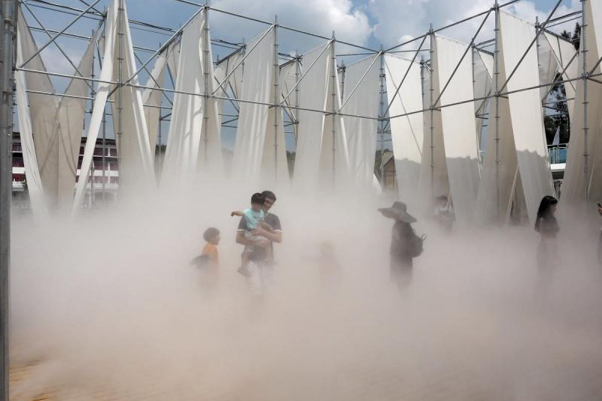 A man holding his daughter walks through mist generated during an art installation called Mist Encounter, a work by Serendipidy and KWA Architects, at the Taipei Fine Arts Museum on July 11, 2017. Taiwan is undergoing a heatwave, with temperatures ne