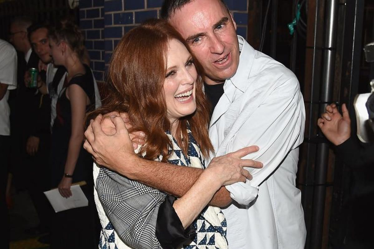 Actor Julianne Moore in a cuddle backstage with designer Raf Simons.