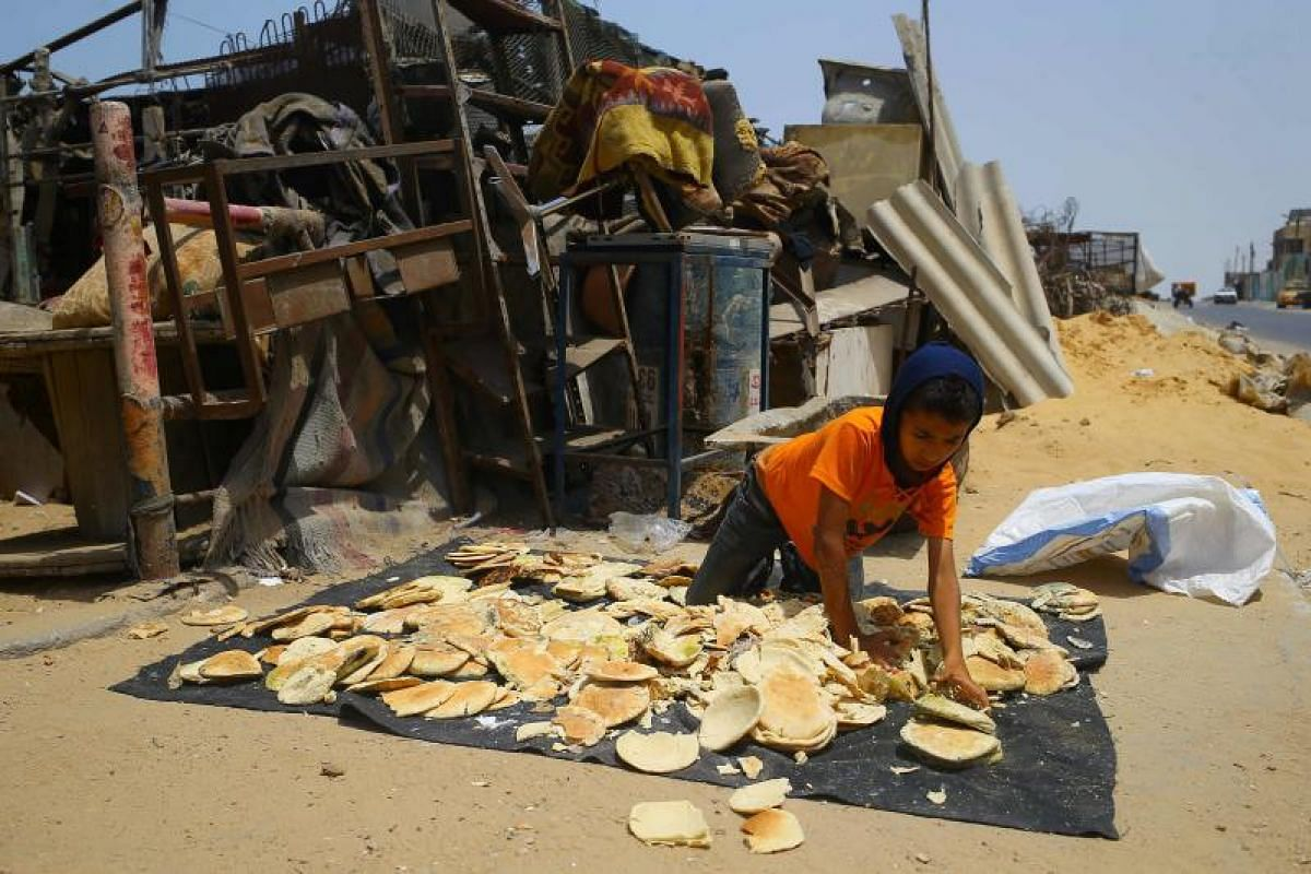 A Palestinian boy spreads old bread on top of a fabric at al-Shatee refugee camp during a heatwave in Gaza City on July 12, 2017.
