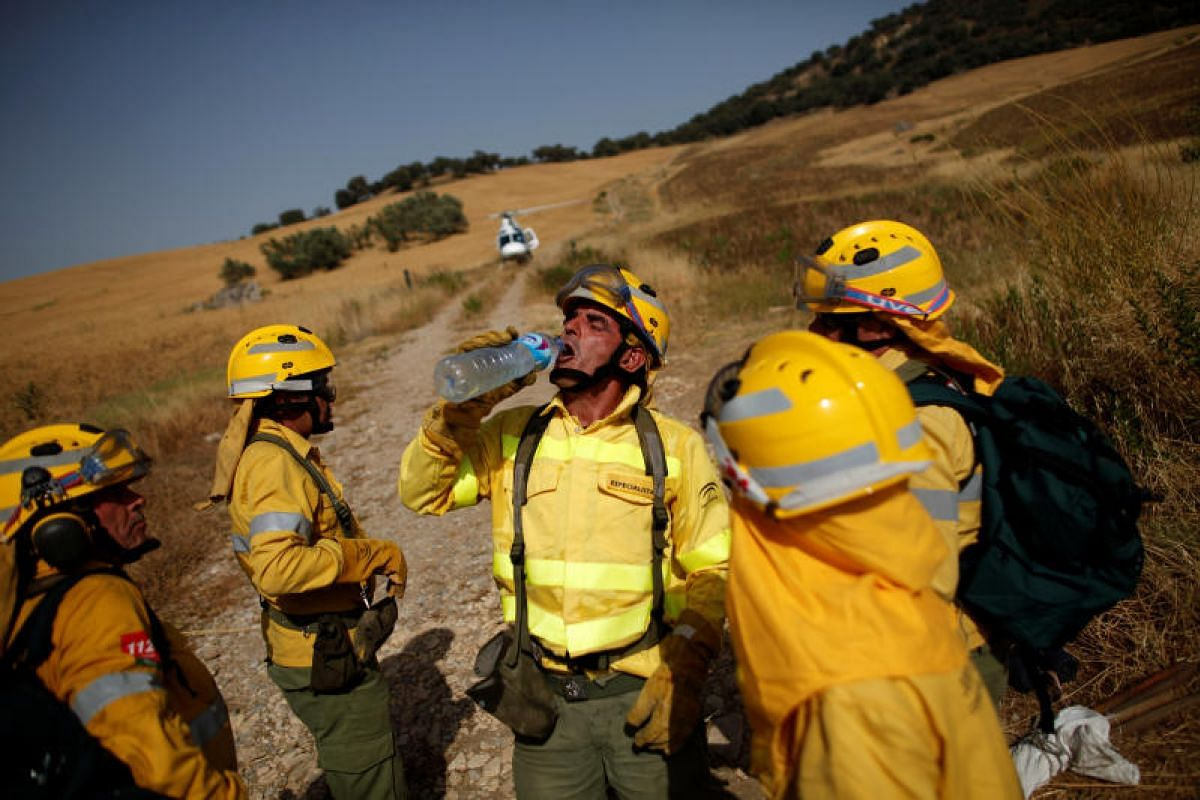 A firefighter drinks water after extinguishing a forest fire during a heatwave in Benaojan, Spain, on July 12, 2017.