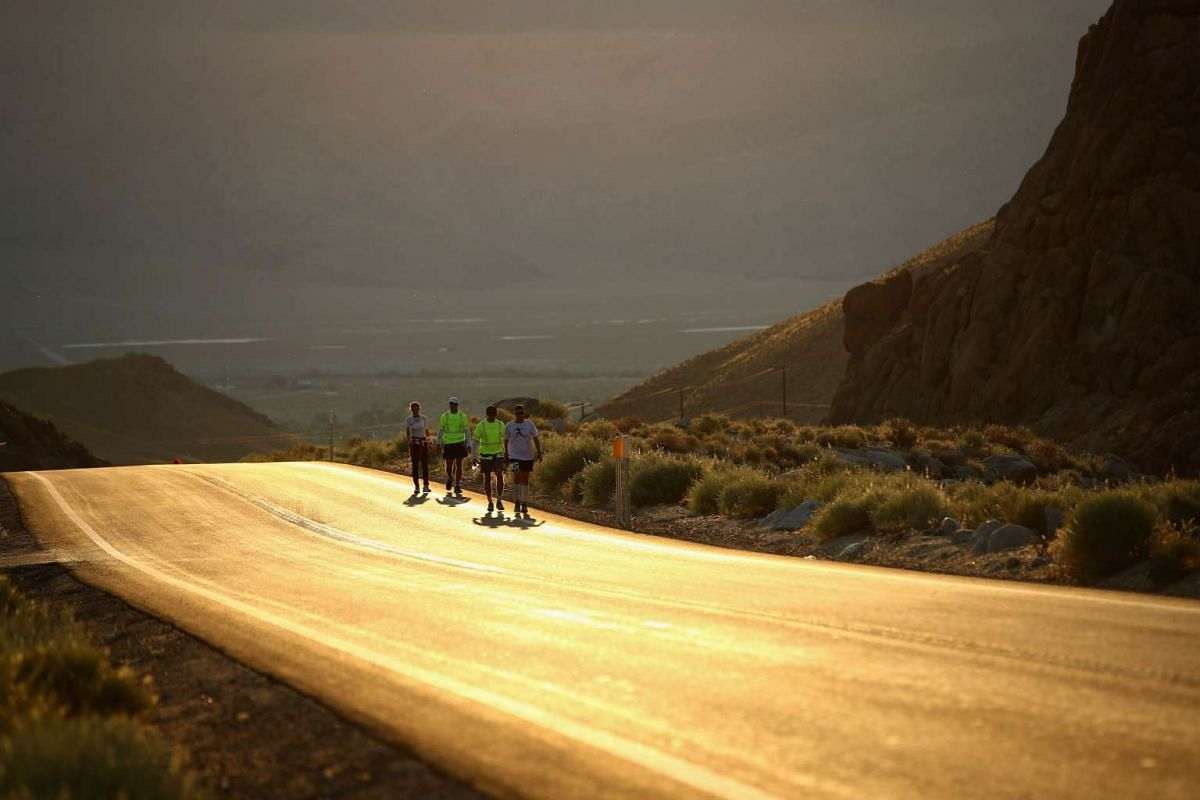 Kyle Fahrenkamp and Szilvia Lubics walk with members of their support team during the second morning of the STYR Labs Badwater 135 on July 12, 2017 in Death Valley, California. The hottest temperature in the world was recorded in Death Valley with a