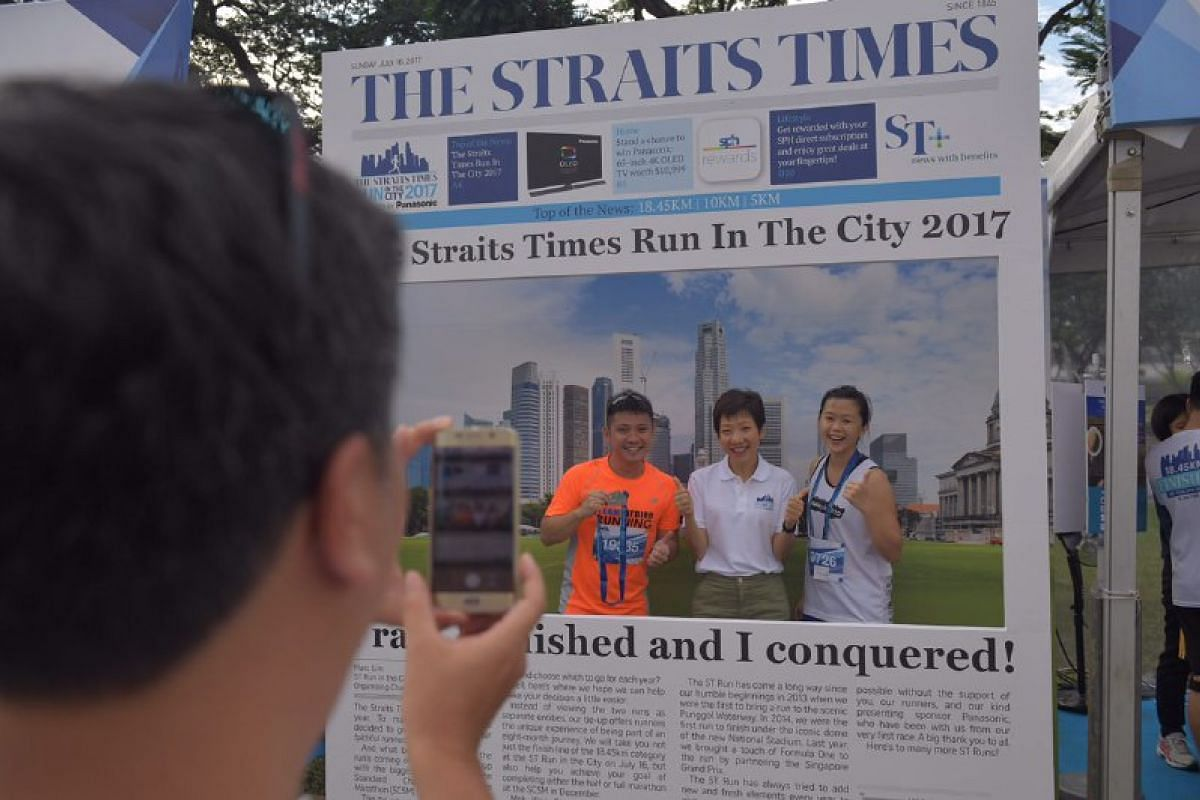 Minister Grace Fu (centre) taking a picture at the photo booth with engineers Too Heng Chen (left), 34, and Cai Huiying, 27.