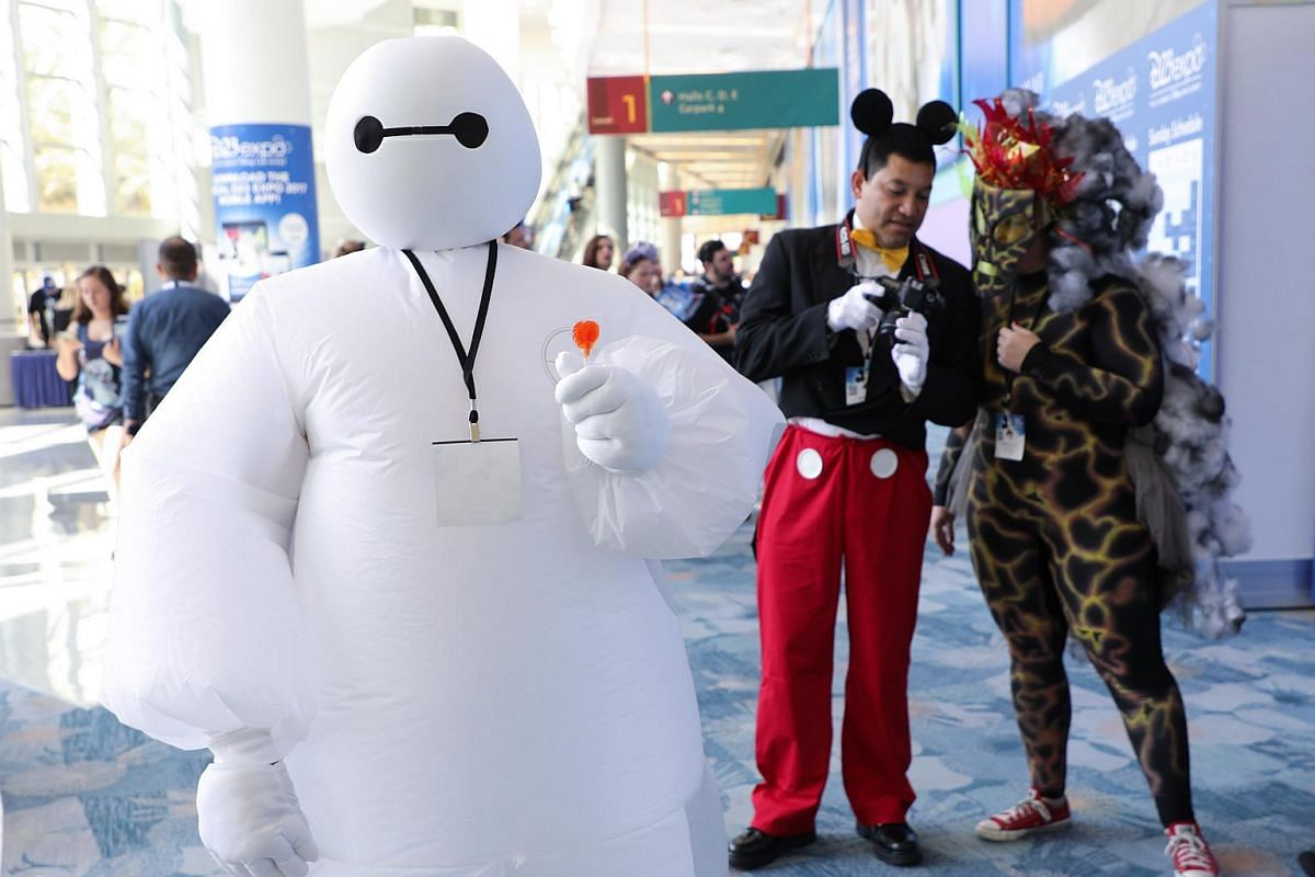 Disney fans pose in their cosplay outfits during the D23 Expo in Anaheim, California on July 15, 2017.