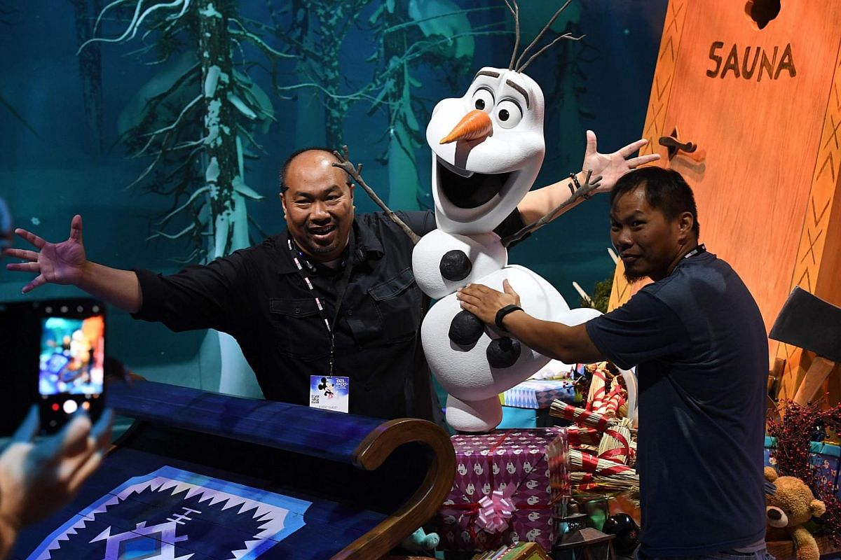 Fans pose for photos with the character Olaf during the D23 expo fan convention at the Convention Center in Anaheim, California, on July 15, 2017.