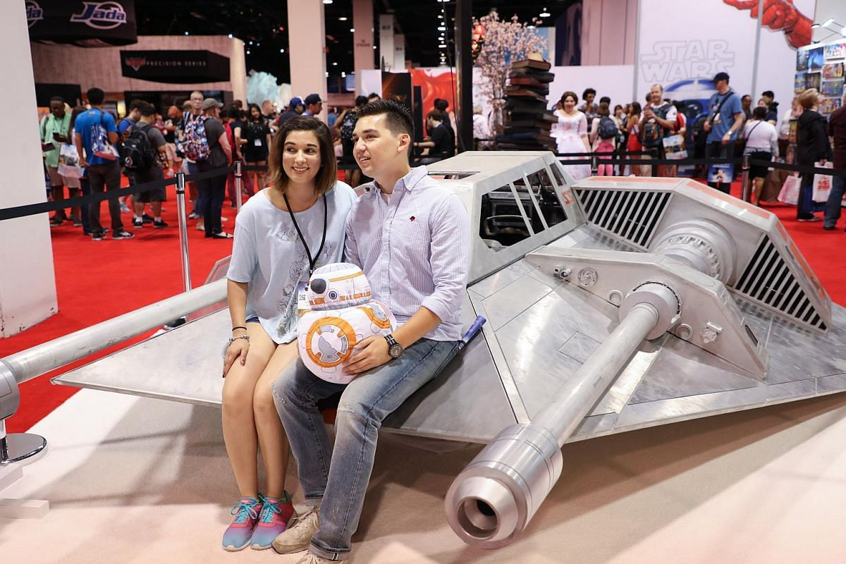 Disney fans pose with a snowspeeder movie prop from the Star Wars films during the D23 Expo in Anaheim, California on July 15, 2017.