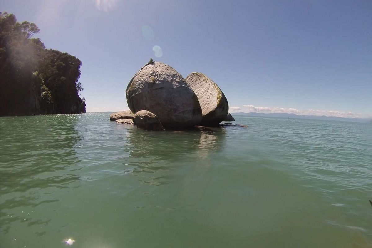 No one knows how Split Apple Rock came to be, but the granite boulder has become a popular tourist attraction in Abel Tasman National Park.