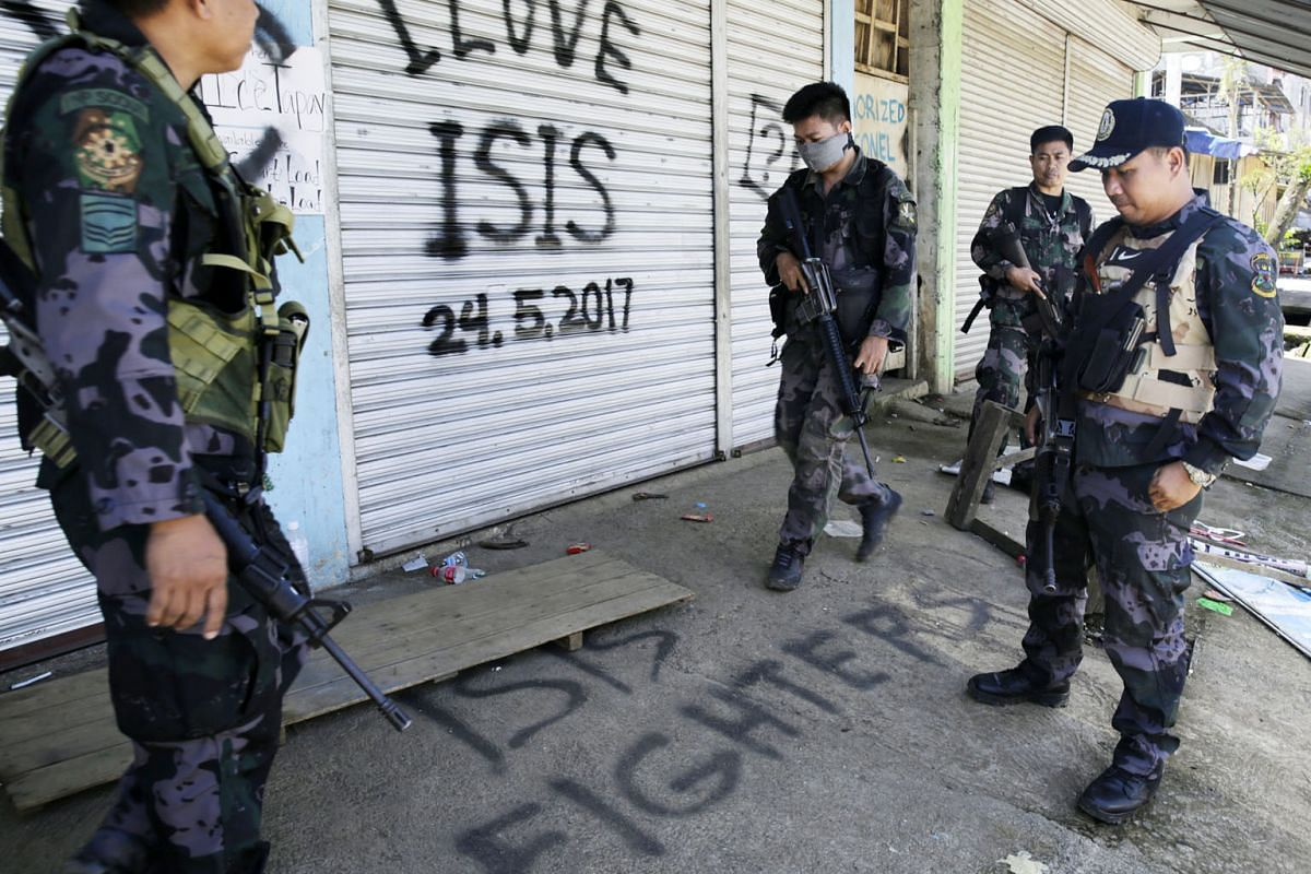 (Top) Members of the Emergency Response Division celebrating ISIS' defeat in Mosul, Iraq, last Saturday. (Above) Philippine troops patrolling a former militant stronghold in Marawi.