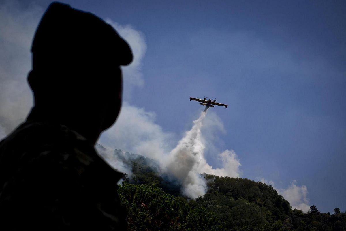 A plane makes a water drop to help fight the fires burning on the Vesuvius volcano, outside Naples, Italy on July 13, 2017.