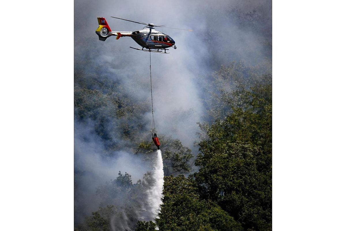 A helicopter makes a water drop to help fight the fires burning on the Vesuvius volcano, outside Naples on July 13, 2017.