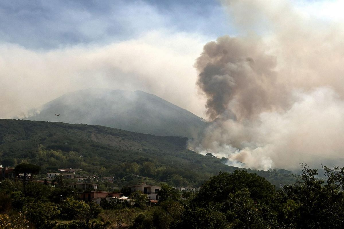 A plane flies above smoke rising from fires on the slopes of Mount Vesuvius east of Naples on July 12, 2017.