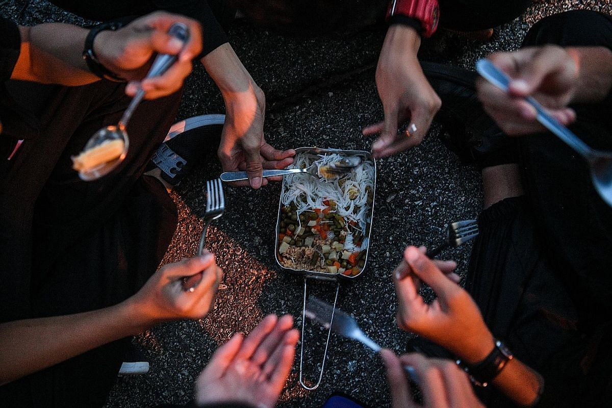 Students eat from a common mess tin during dinner time. Participants are required to cook their own meals for most of the five days and have to ration their food supplies, which include noodles, canned food, bread, isotonic-drink powder sachets and a