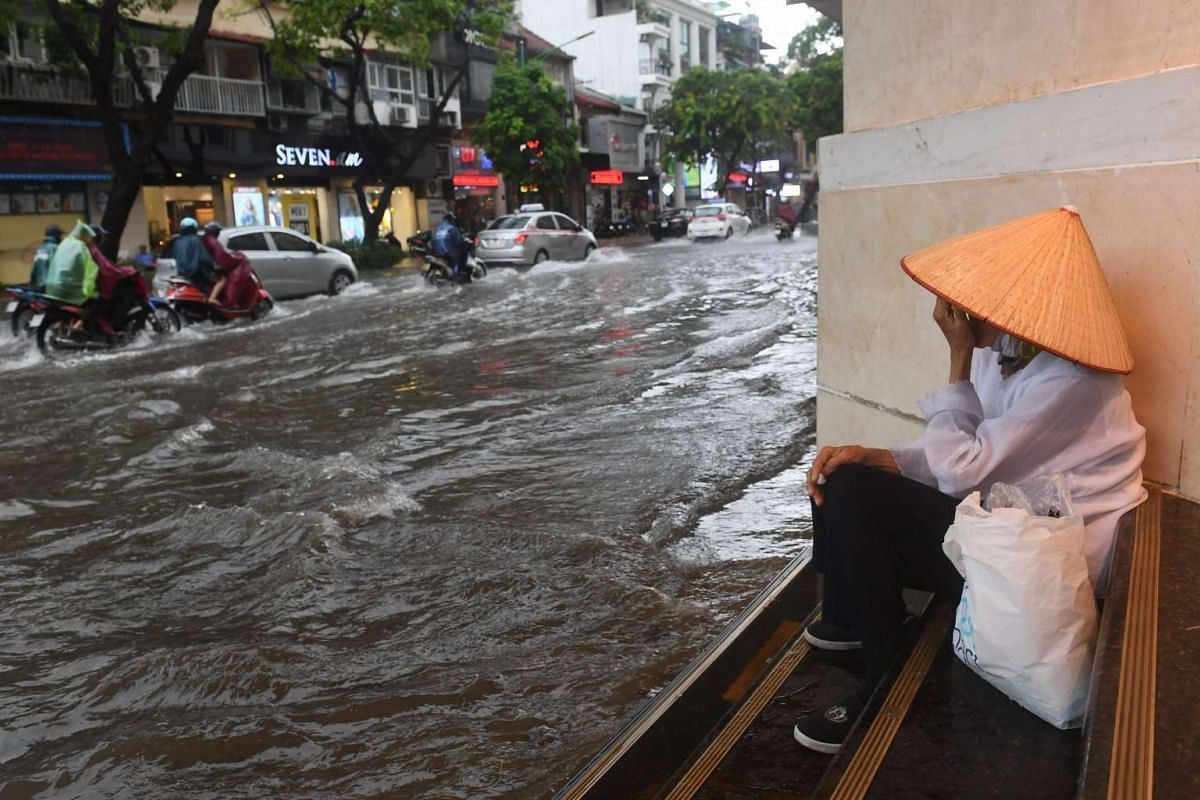 A woman takes shelter from the rain as people commute along a flooded street in Hanoi on July 17, 2017, after tropical storm Talas made landfall in northern Vietnam. PHOTO: AFP