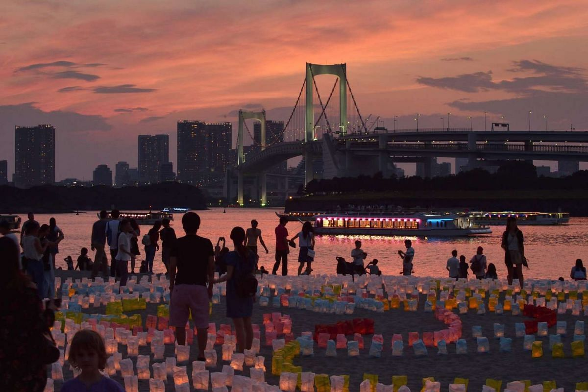 People stand amongst candles lit inside paper lanterns while looking out at Rainbow Bridge (in background) in Odaiba Marine Park in Tokyo on July 17, 2017, as part of a lantern festival. PHOTO: AFP