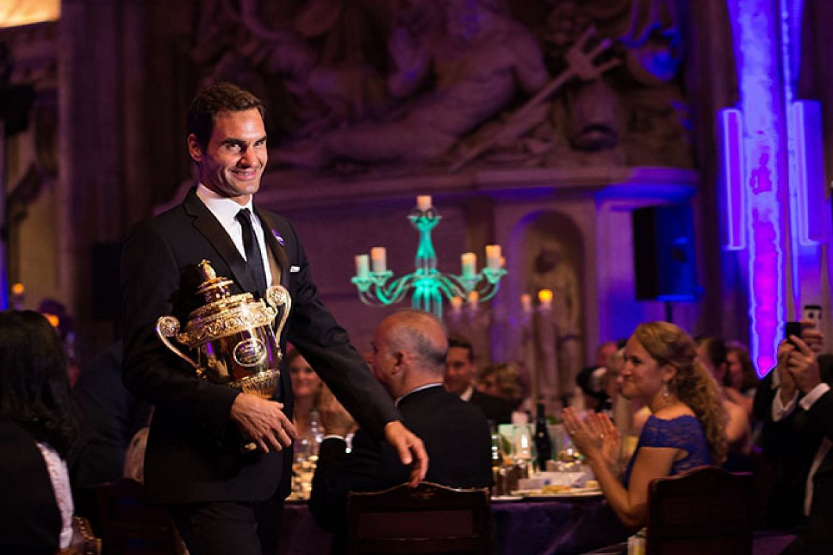 A handout photo made available by the AELTC showing Roger Federer of Swizerland arriving with the men's singles Wimbledon trophy at the Championships Dinner at the Guildhall, London, Britain, July 17, 2017. PHORO: EPA/AELTC