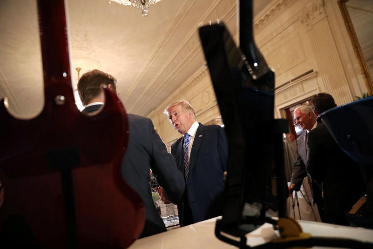 "Mr Trump with business owners at the ""Made in America"" showcase. In the foreground are American-made guitars. PHOTO: REUTERS"