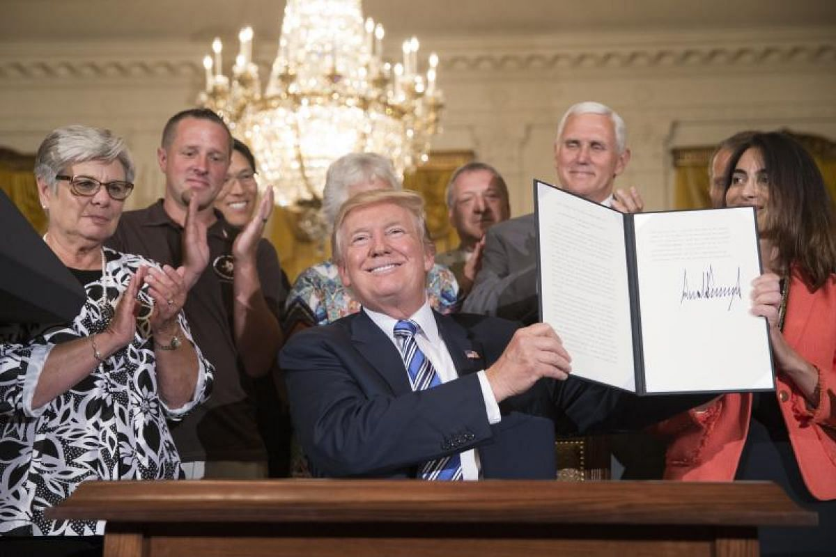 "Mr Trump showing a presidential proclamation that he just signed making Monday (July 17) ""Made in America Day"" and this week, ""Made in America Week"". With him is Vice-President Mike Pence (second from right) and various product representatives. PHOTO"