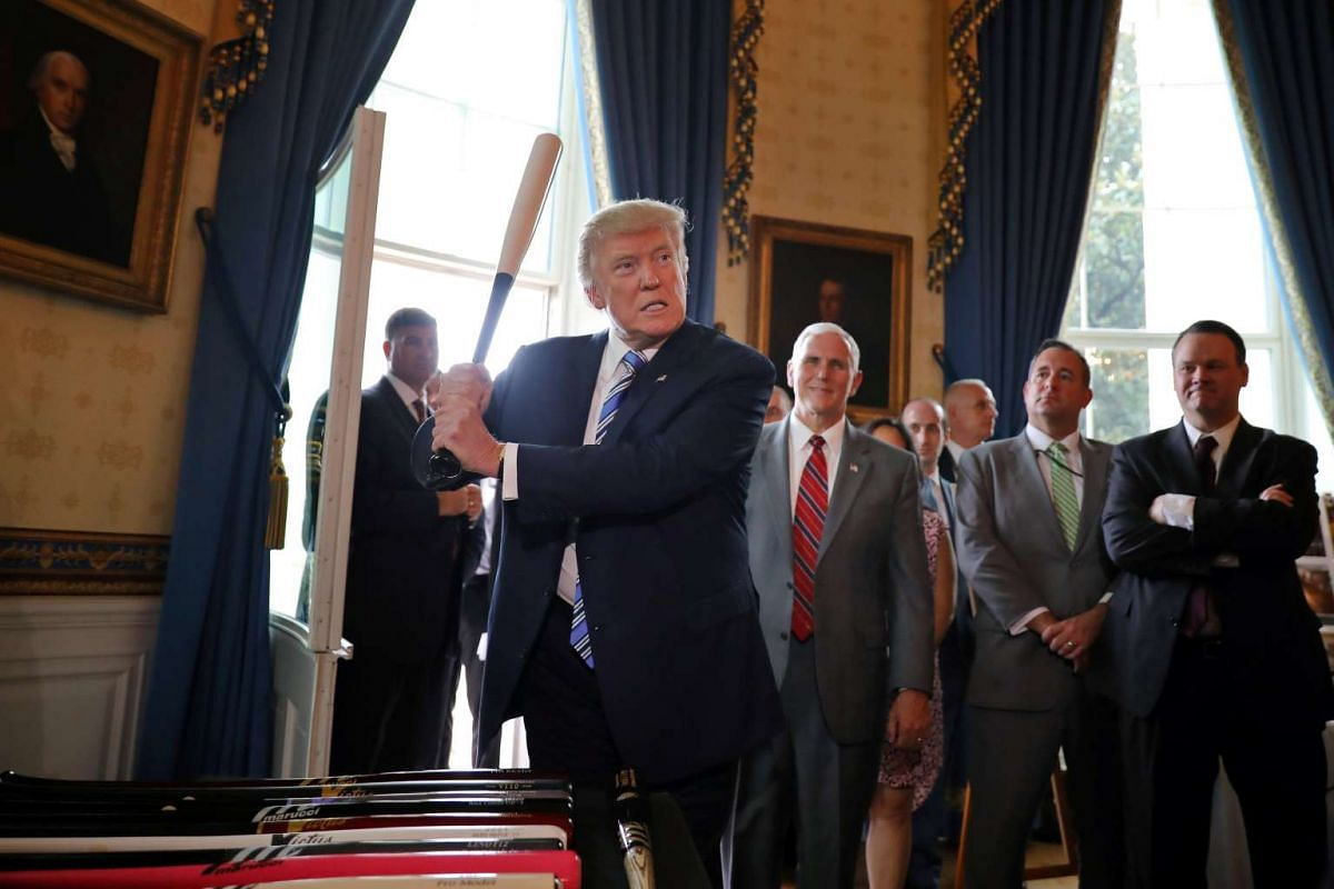 "Mr Trump trying out a baseball bat at the ""Made in America"" product showcase as Mr Pence (red tie) looks on. PHOTO: REUTERS"