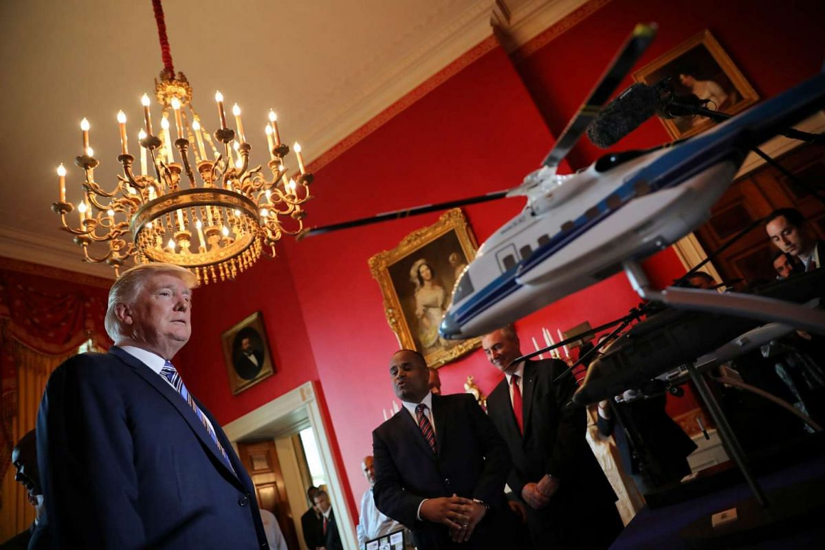 Mr Trump looking at miniature models of helicopters built by American aircraft manufacturer Sikorsky. PHOTO: REUTERS