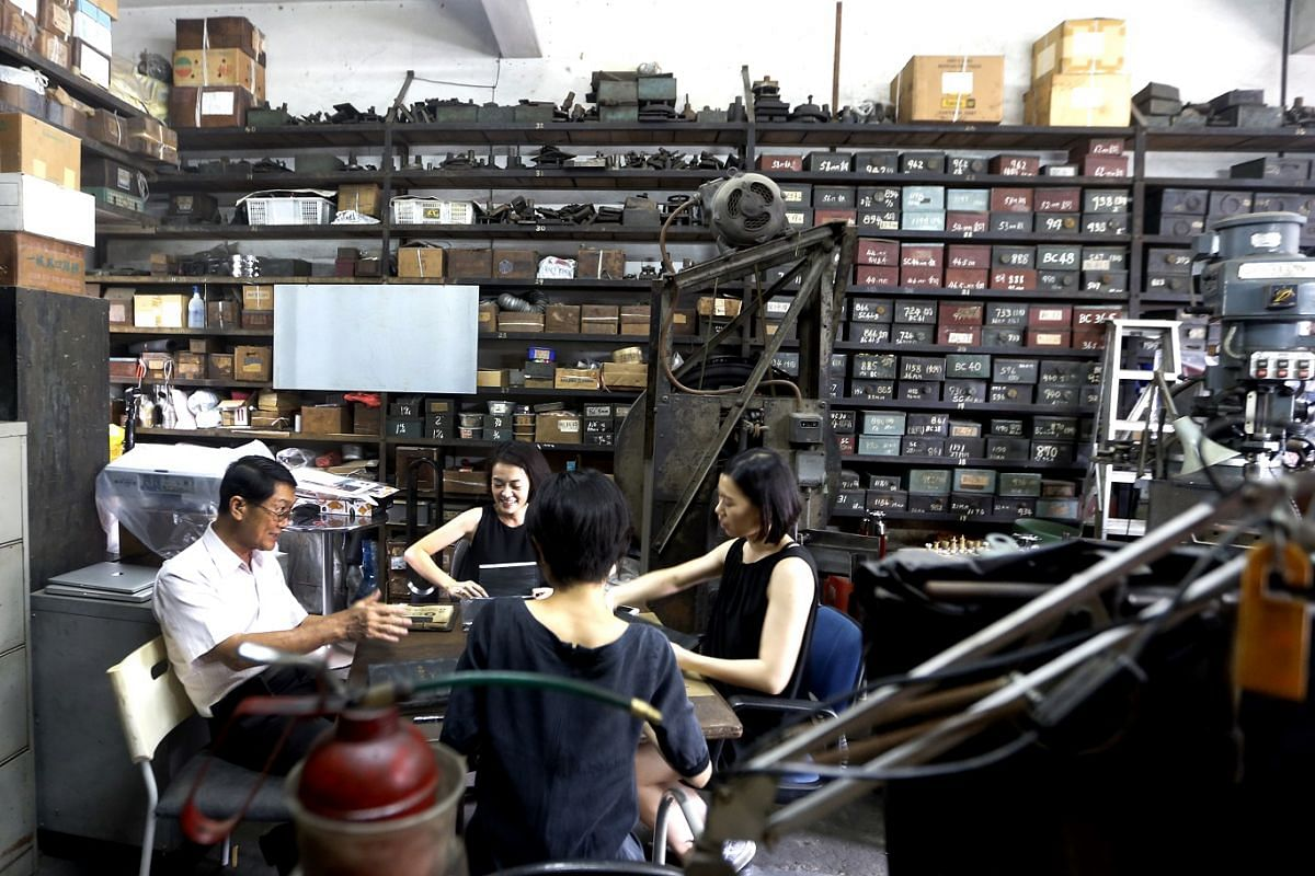 Mr Yee Chin Hoon working with artist Xin Xiaochang (second from left), designer Wendy Chua (right) and jewellery designer Yuki Mitsuyasu (back facing camera) at his shop in Jalan Besar.