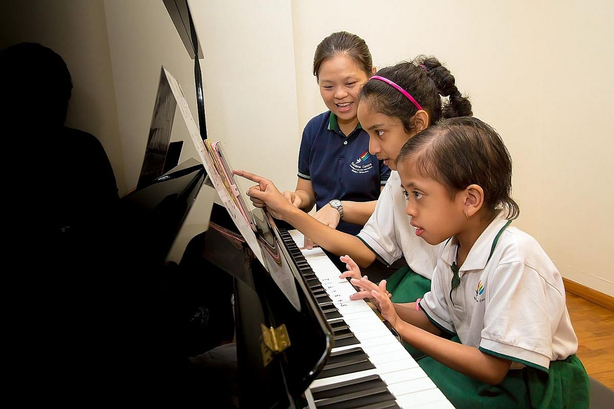 Music therapist Michelle Low (left) has a session with patient Phua Beow Eng at Bright Vision Hospital and children at Rainbow Centre (right) get to play the piano as therapy. St Andrew's Nursing Home resident Tan Chik Neo listens to a personalised p