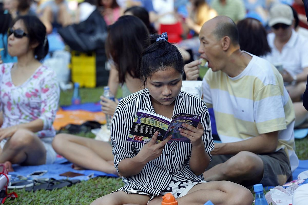 A girl reads a Geronimo Stilton book. Some 2,000 books were donated by Scholastic to attendees at the concert.