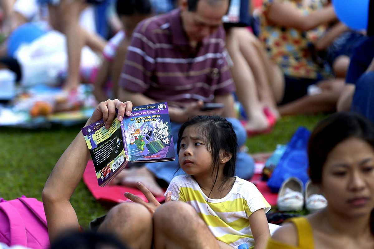 A young girl reads a Geronimo Stilton book at the The Straits Times Concert in the Gardens on July 22.