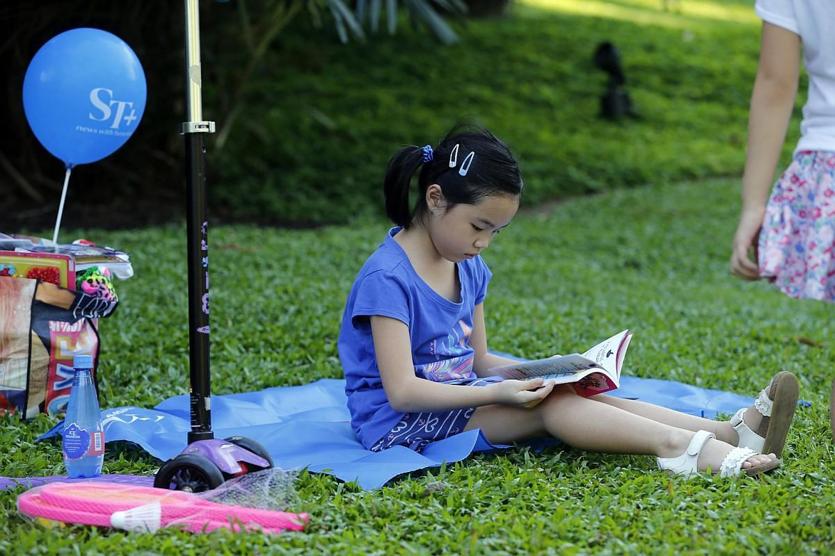 A young girl reads a book at the The Straits Times Concert in the Gardens on July 22. Some 2,000 books were donated by Scholastic to attendees at the concert.
