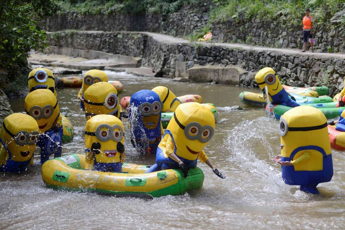 People in Minions costumes cool off at a riverside scenic zone on a hot day in Lianyuan, Hunan province, China July 24, 2017.
