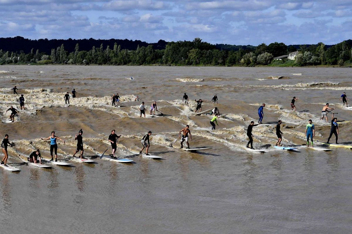People surf and paddle down the Dordogne River during a tidal bore in Saint-Pardon on July 24, 2017. The tidal bore, a large wave resulting from the currents of the ocean tide and the river, occurs several times a year and is caused by large tidal co