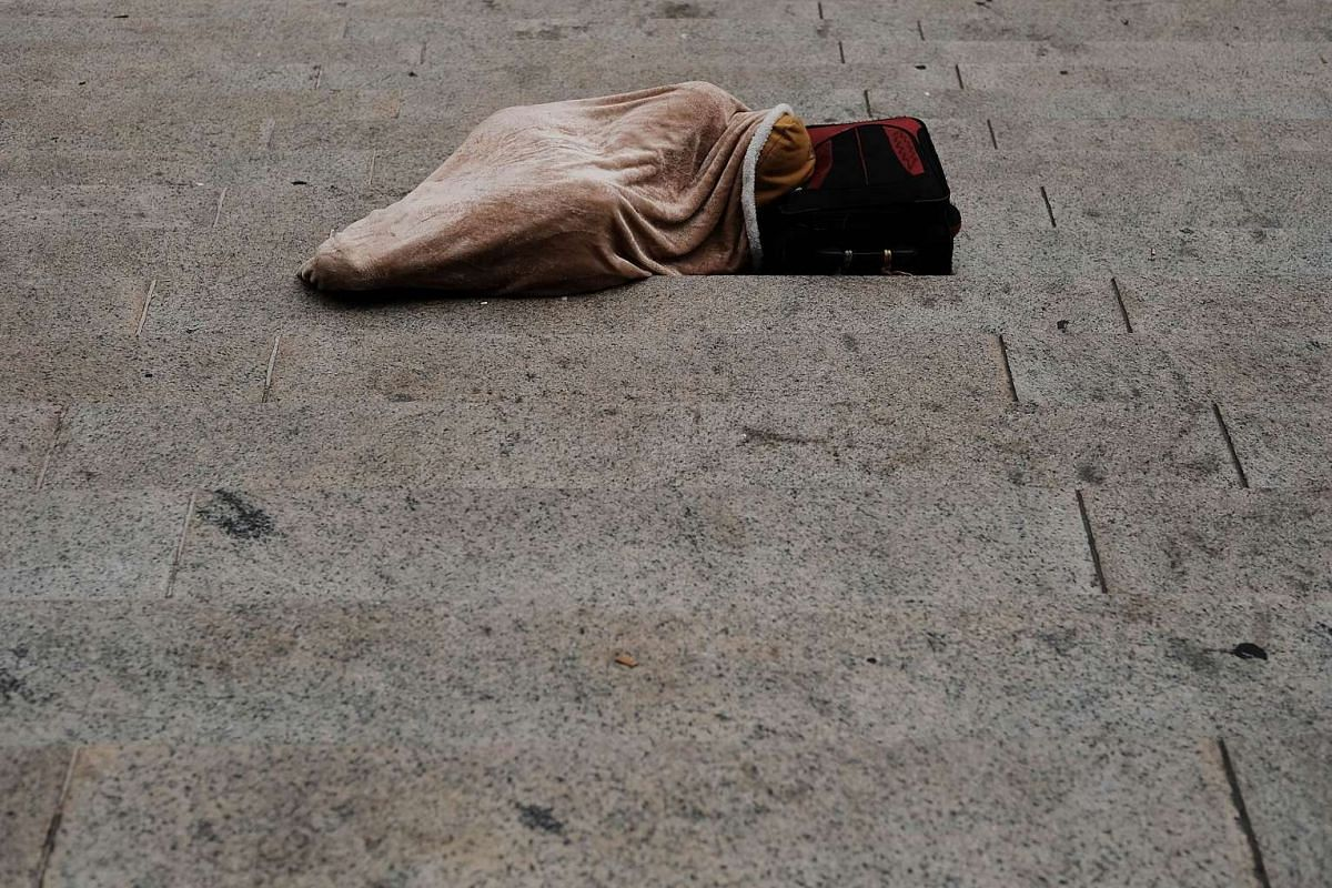 A person sleeps on the street in Manhattan on July 24, 2017 in New York City. In its annual homeless count, New York City recorded 3,892 people living on the streets in February. This is a 40 percent increase in homelessness over 2016 and the highest