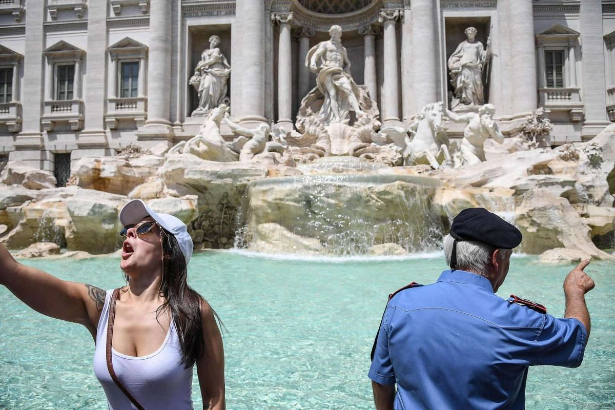 An official monitors members of the public at the start a trial period of a 'controlled transit', with the assistance of two voluntary associations to avoid assembly and any behaviors incompatible with the use of the Trevi fountain, in Rome, Italy. T