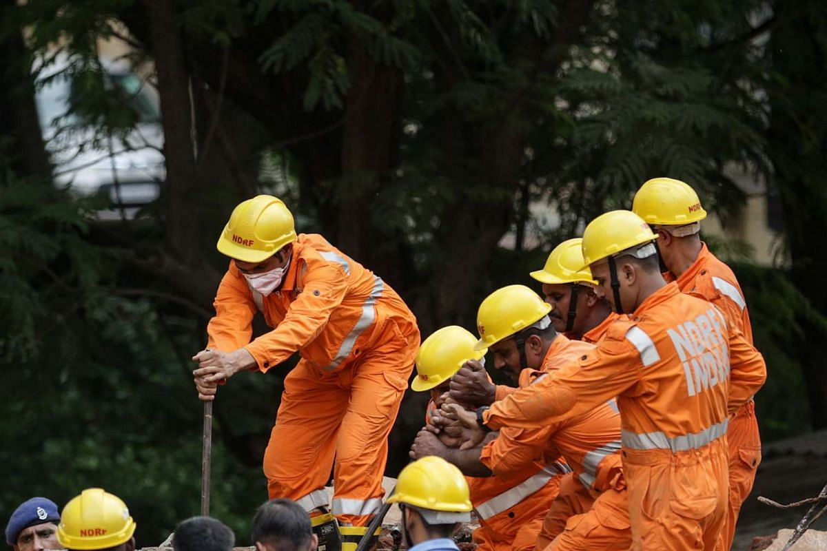 Members of the National Disaster Response Force (NDRF) search for trapped victims under the rubble of a four-storey residential building that collapsed in Mumbai, India, July 25, 2017. According to media reports, some 12 people have died after a coll