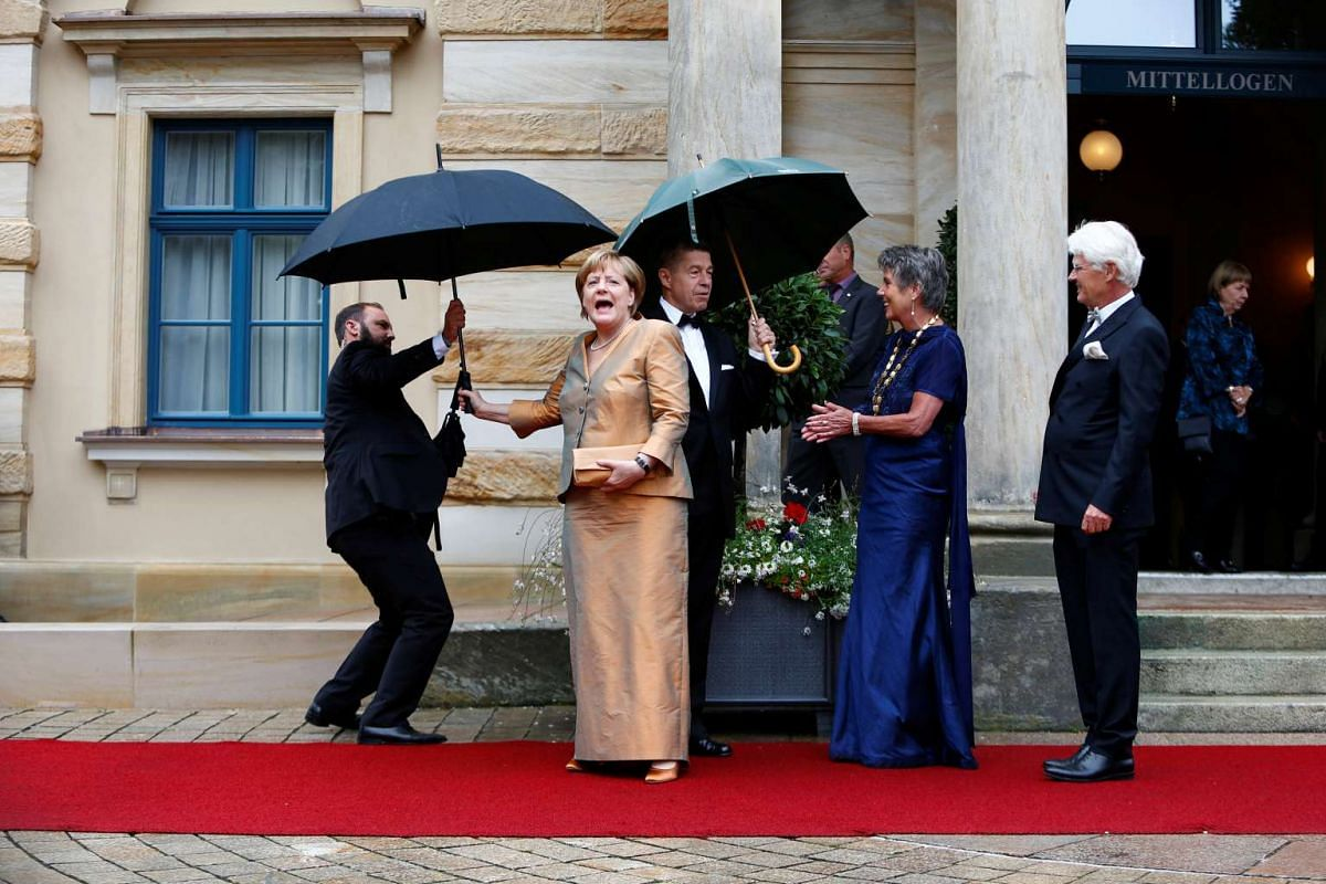 German Chancellor Angela Merkel reacts as she arrives at the red carpet for the opening of the Bayreuth Wagner opera festival outside the Gruener Huegel (Green Hill) opera house in Bayreuth, Germany July 25, 2017.