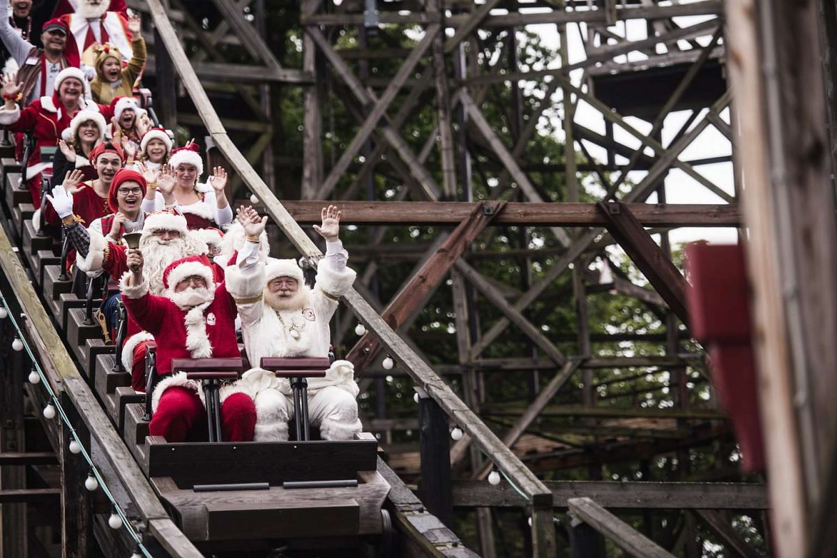 People costumed as Santas enjoying a leisure ride at the amusement park Dyrehavsbakken as part of the annual Santa Claus World Congress, on July 25, 2017.