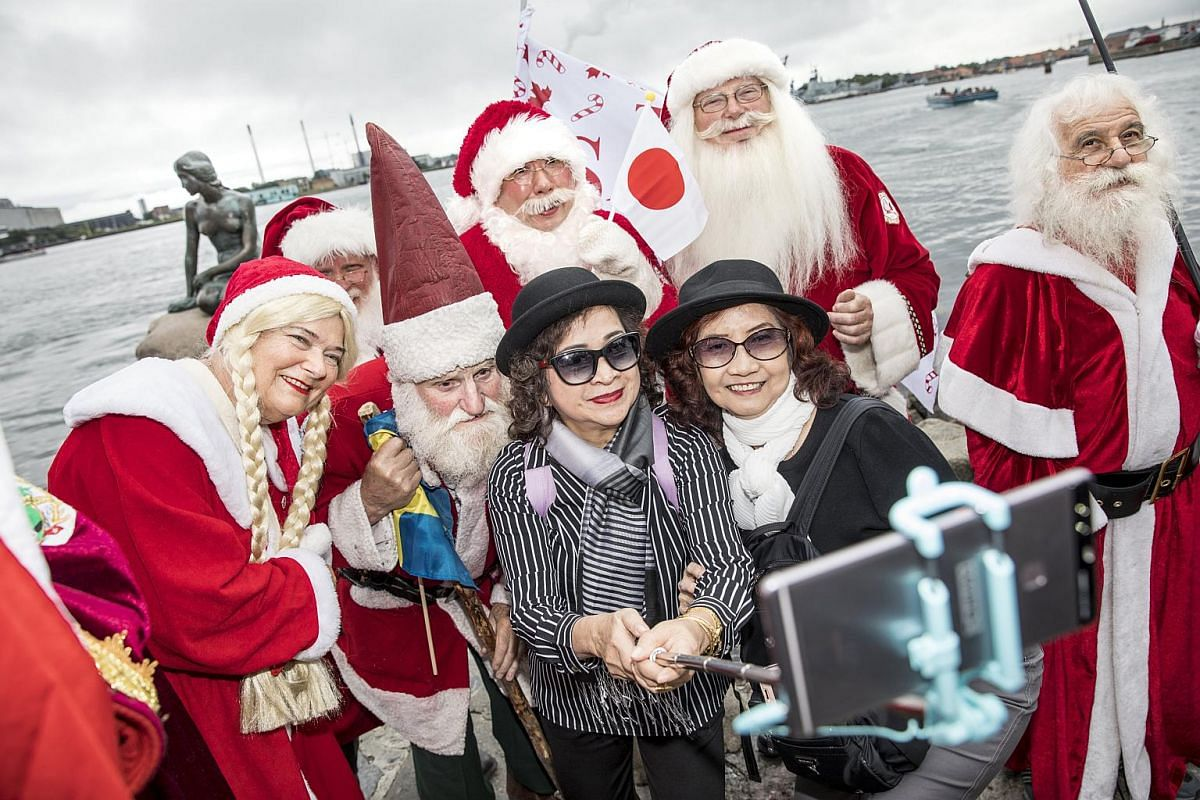 People dressed as Santas taking selfies with tourists while standing in front of the Little Mermaid statue during the annual Santa Claus World Congress in Copenhagen, Denmark, on July 24, 2017.