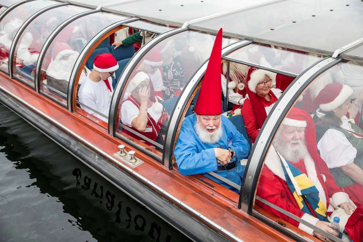 People dressed as Santa Claus taking a canal tour of Copenhagen as they take part in the World Santa Claus Congress, an annual event held every summer at the amusement park Dyrehavsbakken, in Copenhagen, Denmark.