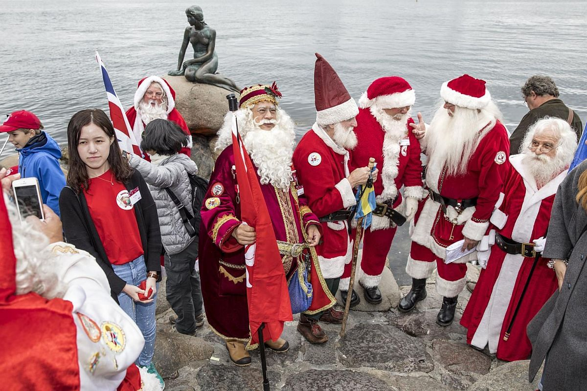 People dressed as Santas standing in front of the Little Mermaid statue, on July 24, 2017.