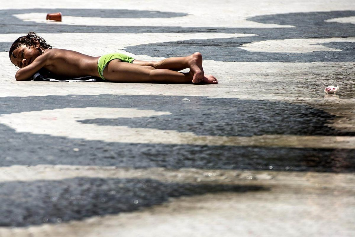 Roma child sunbathes after running through a fountain during a heat wave, on the main square in Skopje, on July 24, 2017.