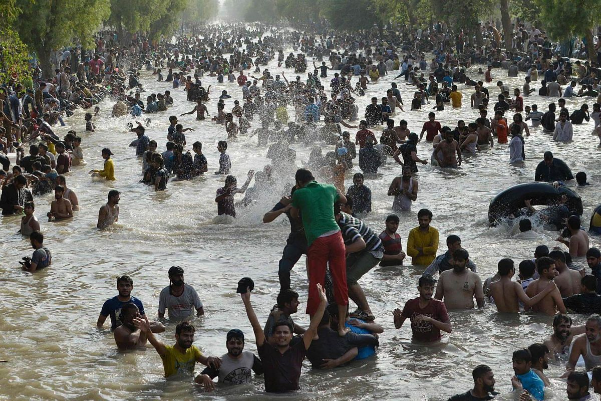 People cool themselves off in a water channel in Lahore during a heat wave on June 4, 2017.