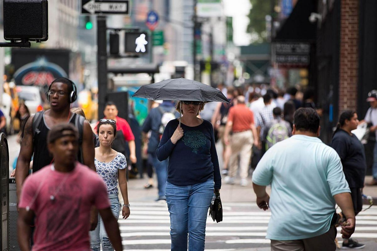 A woman uses an umbrella against the sun in New York City on July 13, 2017.