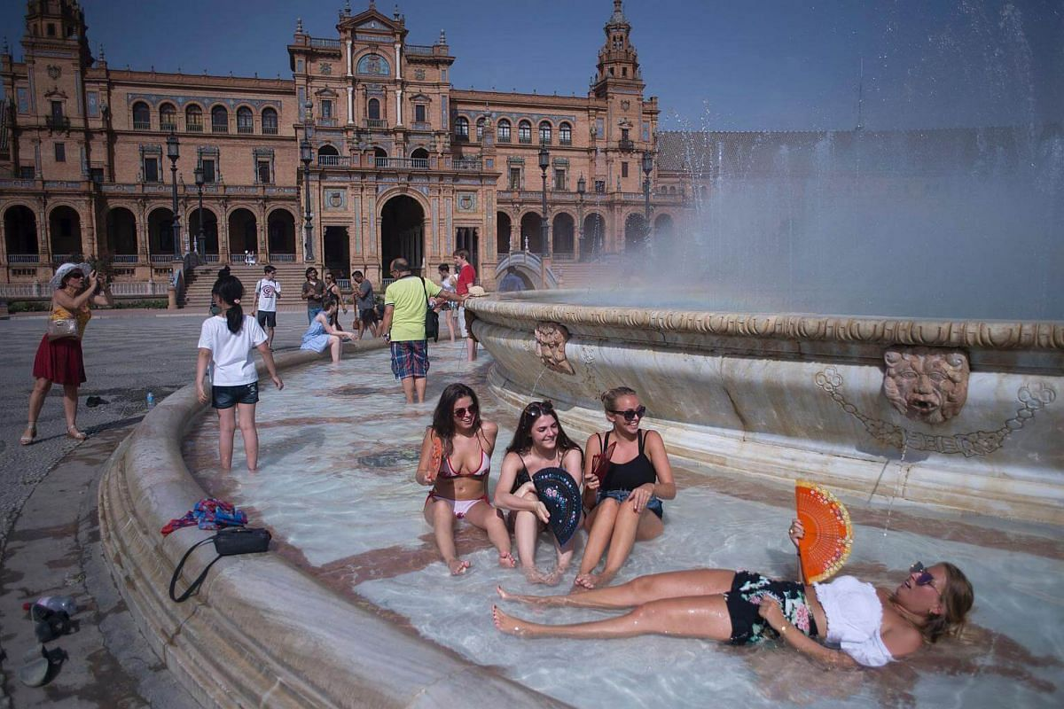 Girls cool off in a fountain of the Plaza de Espana in Sevilla during a heat wave, on July 12, 2017.