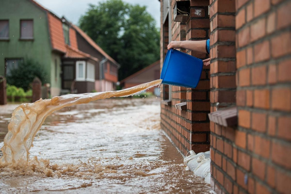 A woman pours water out of her house in Rhueden, northern Germany, on July 26, 2017. Some parts of lower saxony are overflooded after heavy rainfall.