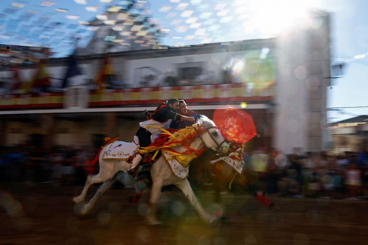 Galloping horse riders clasp one another during the St. James Festival in the village of El Carpio de Tajo near Toledo on July 25, 2017. The spectacle, originally a military training exercise during medieval times using live animals, sees horsemen ga