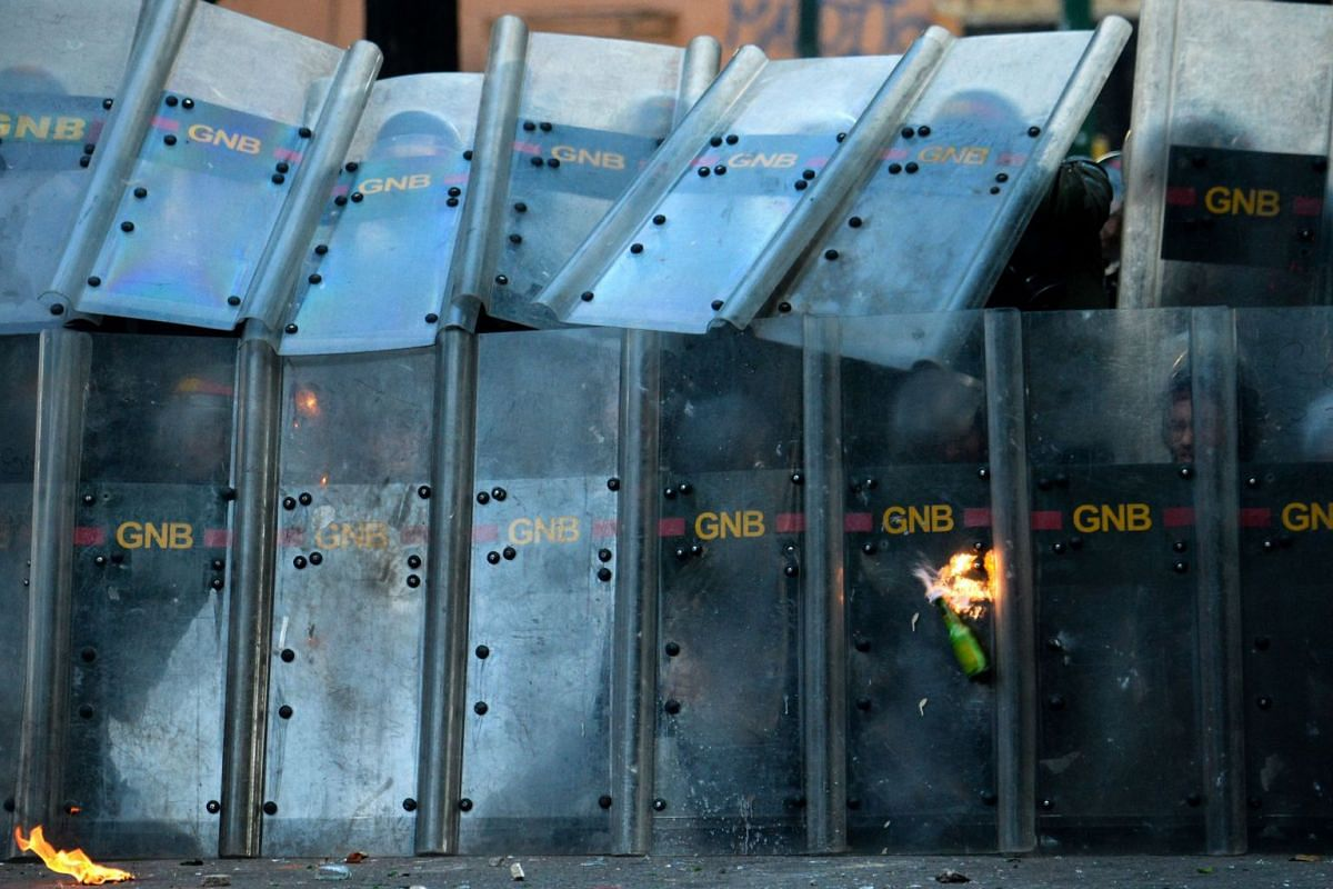 A Molotov cocktail hurled by opposition demonstrators hits a riot police's shield during an anti-government protest in Caracas, on July 26, 2017. Venezuelans blocked off deserted streets Wednesday as a 48-hour opposition-led general strike aimed at t