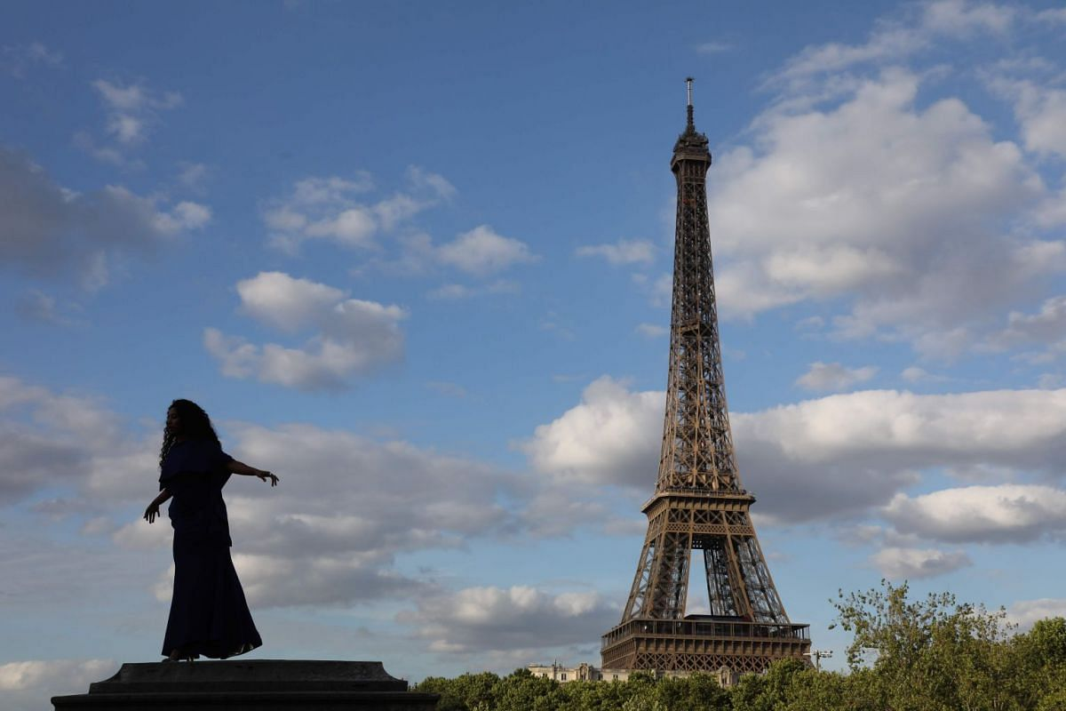 A women wearing a dress poses for pictures on the Bir Hakeim bridge near the Eiffel Tower on July 27, 2017, in Paris.