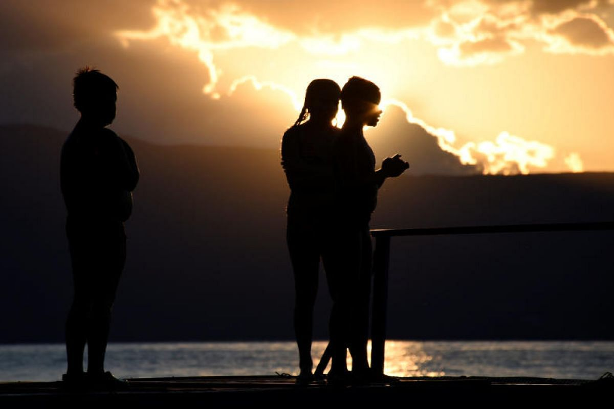 Children watch the sunset in Ohrid, Macedonia on July 27, 2017.